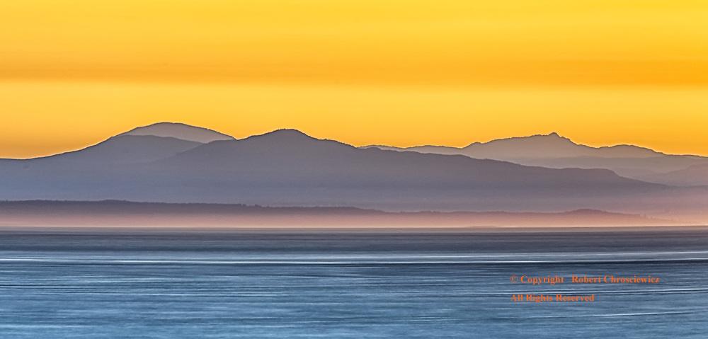 Reflective Line: Light forms a reflective line off the ocean at the base of this silhouette of Vancouver Island, seen at sunset from Vancouver British Columbia Canada.