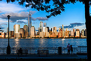 People view the skyline of downtown Manhattan, New York City, seen from the Hudson River, with One World Trade Center, OneWTC.