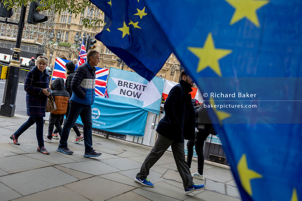 On the day that the EU in Brussels agreed in principle to extend Brexit until 31st January 2020 (aka 'Flextension') and not 31st October 2019, pedestrians walk past Brexit Party flags and banners during a Brexit protest outside parliament, on 28th October 2019, in Westminster, London, England.