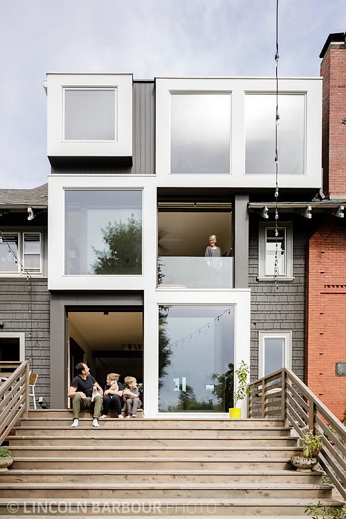 A family sitting on their porch looking up and smiling at the mom in the window.