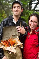 Couple holding bag of Lobster Mushroom found in the forest along the Oregon Coast.