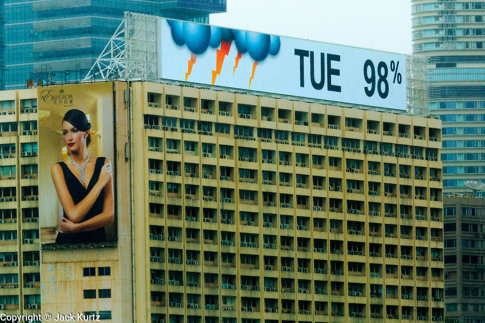 13 AUGUST 2013 - HONG KONG:  A building in Kowloon, Hong Kong shows the weather forecast as 98% chance of thunderstorms during Typhoon Utor. Typhoon Utor (known in the Philippines as Typhoon Labuyo) is an active tropical cyclone located over the South China Sea. The eleventh named storm and second typhoon of the 2013 typhoon season, Utor formed from a tropical depression on August 8. The depression was upgraded to Tropical Storm Utor the following day, and to typhoon intensity just a few hours afterwards. The Philippines, which bore the brunt of the storm, reported 1 dead in a mudslide and 23 fishermen missing at sea. The storm brushed by Hong Kong bringing several millimeters of rain and moderate winds to the island but causing no reported damage or injuries. It is expected to make landfall in China.  PHOTO BY JACK KURTZ