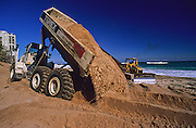 Heavy trucks unload sand to replenish the beach in Singer Island, Florida, United States from erosion. Sand from beach renourishments is often swept back into the ocean, smothering and killing inshore reefs.