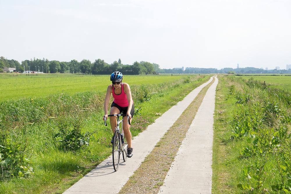 In Maartensdijk rijdt een vrouw op een racefiets door de polder. Van oorsprong een sport die vooral door mannen werd beoefend, doen steeds meer vrouwen aan wielrennen.<br /> <br /> In Maartensdijk a woman is cycling on a road bike.