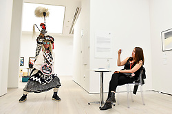 © Licensed to London News Pictures. 12/09/2018. LONDON, UK. A staff member watches artist Frog King Kwok (Hong Kong) posing at the preview of START, a contemporary art fair comprising eclectic works from a variety of international emerging artists.  The fair takes place at the Saatchi Gallery in Chelsea 13 to 16 September 2018.  Photo credit: Stephen Chung/LNP