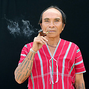 Portrait of a Karen Pwo ethnic minority man smoking a pipe at Mae Lay village, Chiang Mai province, Thailand