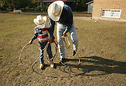 """A father teaches his son """"cowboy tricks"""" with a """"soga,"""" (rope). (Betty Udesen / The Seattle Times)"""