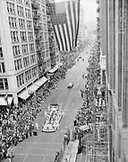 """Rose Festival crowds at SW 6th & Alder, looking south on 6th.  Pioneer Courthouse on left. June 9, 1950. """"Crowds numbering into the thousands swept into the street after the parade passed each of the many blocks along its route. In this view, looking south on Sixth Avenue from Alder street, the massed throngs completely fill the wide street from building to building. This photograph was taken from one of the platforms erected by crews demolishing the old Oregonian building."""""""