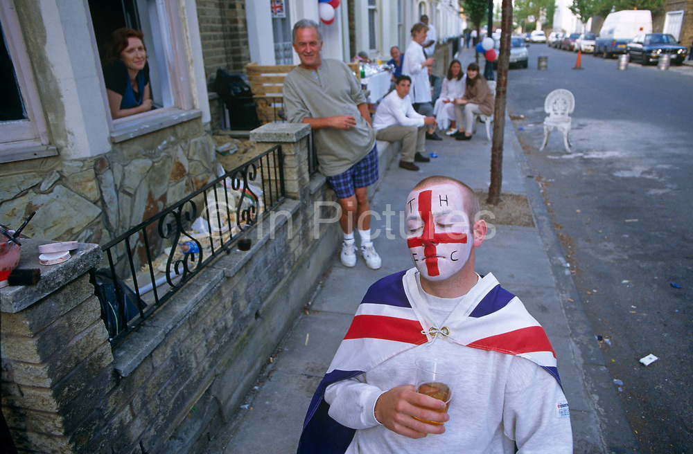 Sitting in chair outside his house in the East End of London, a young football fan waits for his painted face to dry. In the colours his favourite Tottenham Hotspur Football Club, he also wears a Union Jack cape. He sits with an outdoor party behind him in full swing that celebrates the 50th anniversary of VE (Victory in Europe) Day on 6th May 1995. In the week near the anniversary date of May 8, 1945, when the World War II Allies formally accepted the unconditional surrender of the armed forces of Germany and peace was announced to tumultuous crowds across European cities, the British still go out of their way to honour those sacrificed and the realisation that peace was once again achieved. Street parties now – as they did in 1945 – played a large part in the country's patriotic well-being.