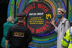 Two environmental activists from Extinction Rebellion are pictured glued onto a 'plaque of shame' outside the offices of law firm Maples Group during a Blood Money March through the City of London on 27th August 2021 in London, United Kingdom. Extinction Rebellion were intending to highlight financial institutions funding fossil fuel projects, especially in the Global South, as well as law firms and institutions which facilitate them, whilst calling on the UK government to cease all new fossil fuel investment with immediate effect.