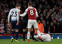 Football - 2018 / 2019 Premier League - Arsenal vs. Tottenham Hotspur<br /> <br /> Alexandre Lacazette (Arsenal FC) lays injured as Christian Eriksen (Tottenham FC) looks on at The Emirates.<br /> <br /> COLORSPORT/DANIEL BEARHAM