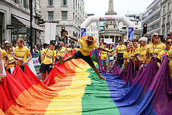 © Licensed to London News Pictures. 06/07/2019. London, UK. A participant jumps over the rainbow coloured Pride flag at the annual Pride Parade in central London. An estimated over 1 million people lined along the route in support of the LGBT (Lesbian, Gay, Bisexual and Transgender/Transsexual) community. Photo credit: Dinendra Haria/LNP