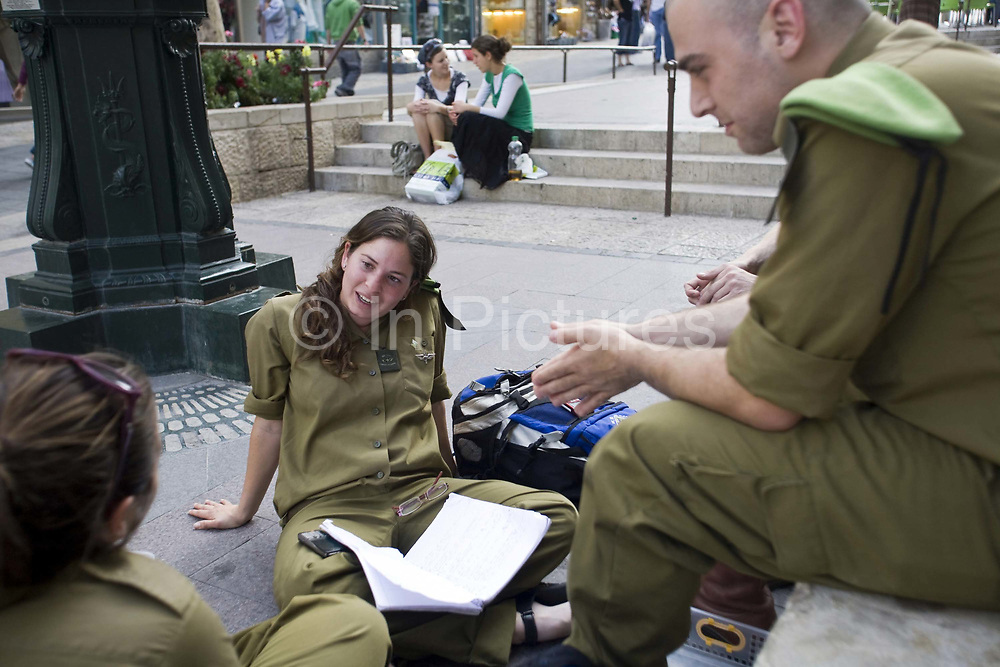 Off duty soldiers sit and talk on some steps in Ben Yahuda Street, Jerusalem, Israel