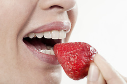 Close-up of a mature woman eating strawberry, Bavaria, Germany