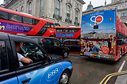 The southern French city of Marseille appears as an advert on the rear of a London tour bus travelling through the capitals streets, through a wet Piccadilly Circus. In almost gridlocked traffic at this busy central London road junction, the bus is showing its content to other drivers and passengers, a visual billboard on the move through the capital, urging Londoners where to spend their holidays.