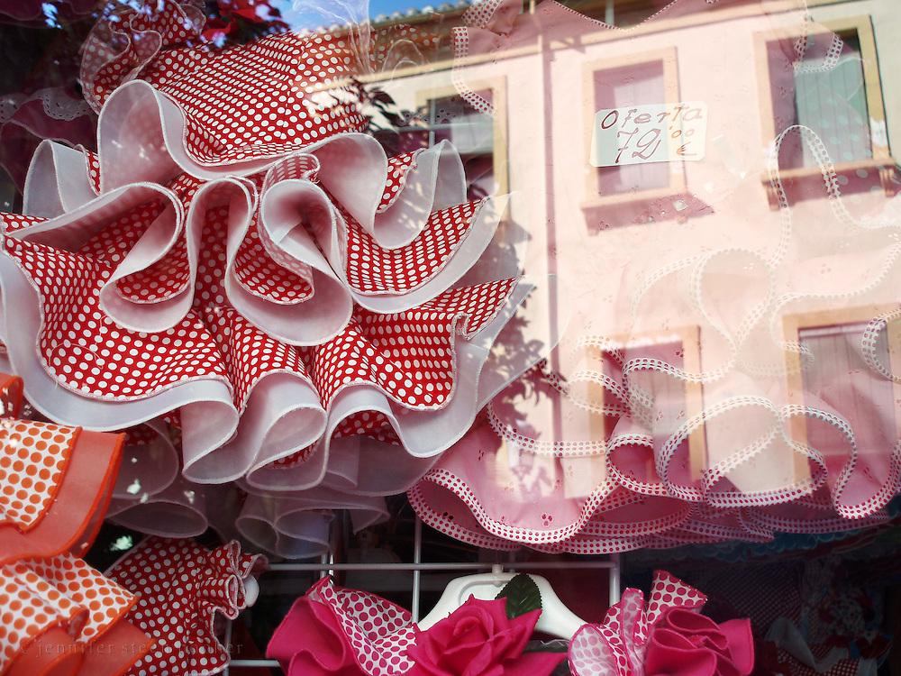 Reflections in a shop window displaying children's flamenco-style dresses, Granada, Spain.