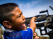 """14 JANUARY 2017 - BANGKOK, THAILAND: A Thai child plays with a FN MAG machine gun during Children's Day activities at the King's Guard, 2nd Cavalry Division base in Bangkok. Thailand National Children's Day is celebrated on the second Saturday in January. Known as """"Wan Dek"""" in Thailand, Children's Day is celebrated to give children the opportunity to have fun and to create awareness about their significant role towards the development of the country. Many government offices open to tours and military bases hold special children's day events. It was established as a holiday in 1955.        PHOTO BY JACK KURTZ"""