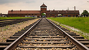 Rail tracks and entrance gate to the Auschwitz-Birkenau concentration camp, Auschwitz, Poland