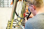 Een fietsenmaker richt een wiel. In Nijmegen is in het oude Honig complex het Fietscentrum Nijmegen (FCN) gevestigd.  Het FCN biedt onderdak aan onder andere Elan ligfietsen, fixie- en designfietsenwinkel Stipbike, een racefietswinkel en fietsverhuur Mastworp. Het FCN wil de fiets als een breed inzetbaar en duurzaam vervoermiddel laten zien. Je moet er niet alleen terecht kunnen voor de modernste en mooi vormgegeven fietsen, het centrum moet ook een ontmoetingsplaats worden voor de fietsliefhebber en platform zijn voor de verdere ontwikkeling van de fiets.<br /> <br /> In Nijmegen in the old Honig complex the Bike Centre Nijmegen (Fiets centrum Nijmegen FCN) is located. The FCN hosts amongst others Elan recumbent bikes, fixie and design bike shop Stipbike, a road bike shop and bike rental service Mastworp. The FCN wants to show the bicycle as a versatile and sustainable transport medium. The center not only gives visitors a chance to see the modern and well-designed bicycles, it should be a meeting place for the bike enthusiast and platform for the further development of the bicycle.