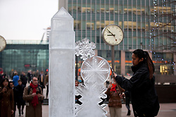© Licensed to London News Pictures. 10/01/2013. London, UK. Ice sculptor Annemarie Taberdo puts the finishing touches to a sculpture featuring One Canada Square at the launch of the London Ice Sculpting Festival in Canary Wharf, London, today (10/01/12). The festival, in its fifth year, is free to members of the public and runs from the 11th to the 13th of January at Canary Wharf. Photo credit: Matt Cetti-Roberts/LNP