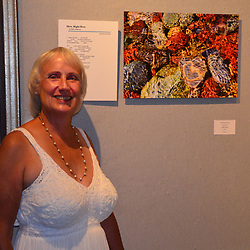 """Janet MacCausland stands before her image """"Heart Rock"""", along side the poem written to accompany it, in the Wickford Art Gallery opening night. Heart Rock is the opening image in the annual Wickford Art Association's """"Poetry and Art"""" book."""