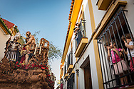 Children look the passage of a float carrying a scene from the bible. Each procession usually has 2 floats, the first carrying Jesus Christ, the second Virgin Mary. Cordoba, Spain.
