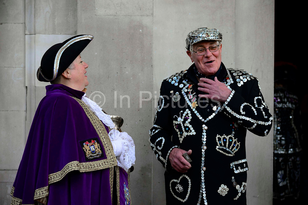 A Pearly King laughs with a town crier outside St Martin-in-the-Fields church ahead of a service  for the Pearly Kings and Queens annual Harvest Festival on 6th October 2019 in London, United Kingdom. The tradition of the Pearly Kings and Queens originated in the 19th century when London street sweeper Henry Croft decorated his uniform and began collecting money for charity. The annual harvest festival sees Pearly Kings and Queens gather to celebrate the autumn harvest with a church service.