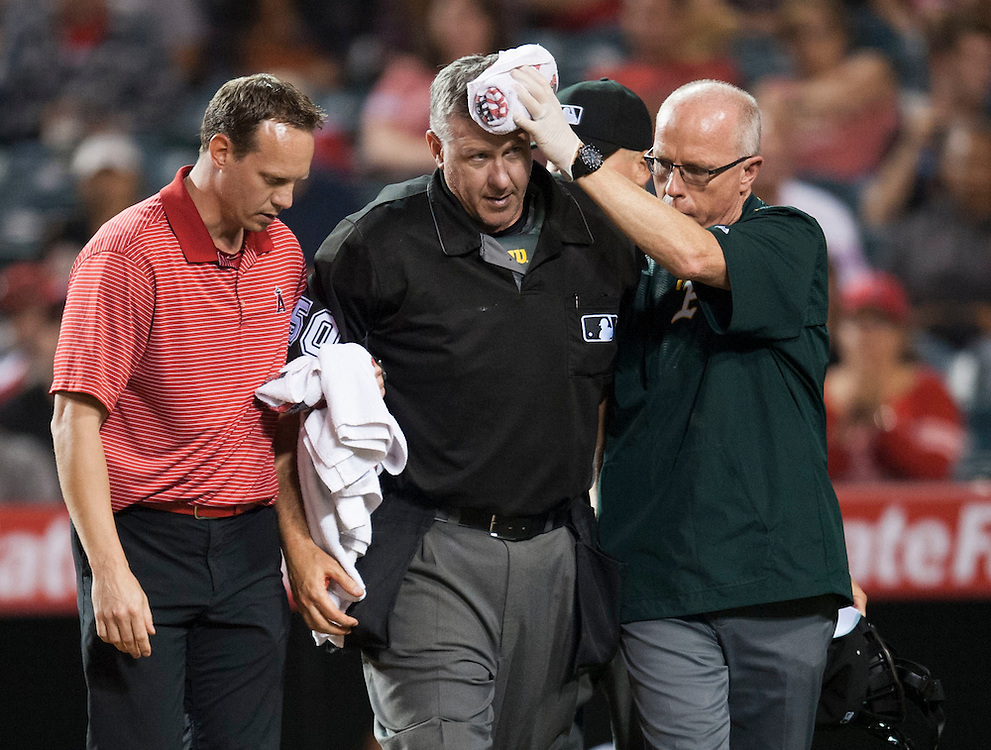 Home plate umpire Paul Emmel is helped off the field after being hit in the head by the bat of Jefry Marte in the ninth inning during the Angels' 5-4 loss to the Oakland Athletics at Angel Stadium on Thursday.<br /> <br /> ///ADDITIONAL INFO:   <br /> <br /> angels.0624kjs  ---  Photo by KEVIN SULLIVAN / Orange County Register  --  6/23/16<br /> <br /> The Los Angeles Angels take on the Oakland Athletics Thursday at Angel Stadium.<br /> <br /> <br />  6/23/16