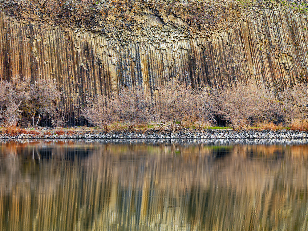 Columnar basalt exhibits massive, vertically standing columns. Although usually hexagonal (six-sided), such columns are polygonal (multi-sided) and may have anywhere from three to 12 sides. They are often so uniform in size and shape that they seem to have been artificially constructed, like giant columns of poured concrete. Snake River Hells Canyon near Asotin.  Licensing and Limited Edition Prints.