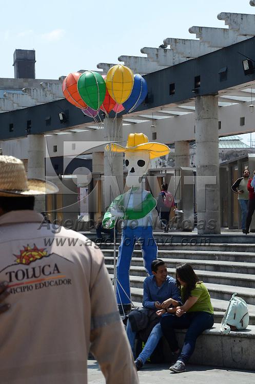 Toluca, Méx.- Trabajadores del ayuntamiento de Toluca, colocaron en la explanada de la plaza González Arratia figuras de calaveras con imágenes de bolero, barrendero, globero, policía entre otros, en vísperas del Día de Muertos. Agencia MVT / José Hernández