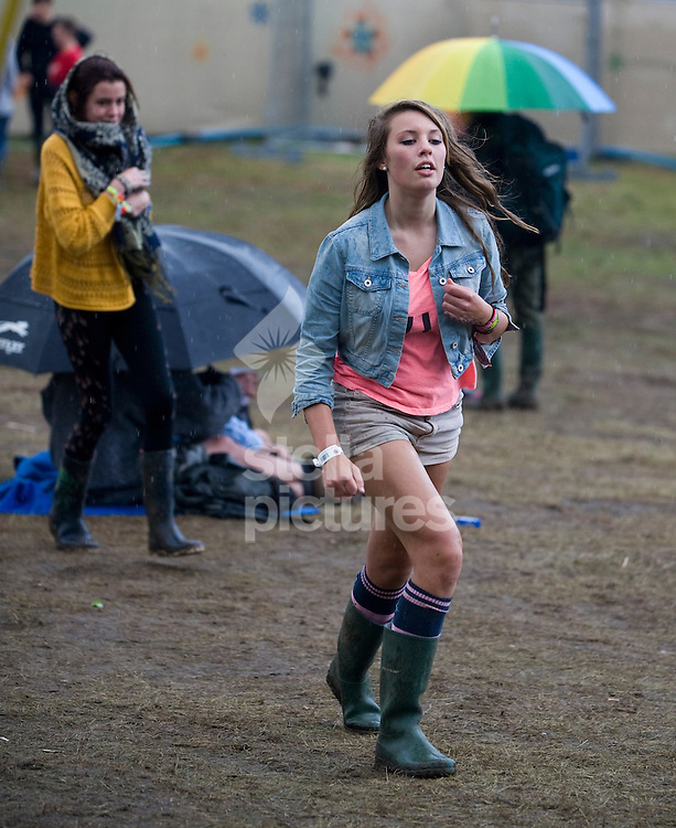 Picture by Daniel Hambury. .17/7/11..A festival goer runs for cover during a rain storm at Latitude, a music and arts festival set on the Henham Estate in Suffolk..The event runs from July 14th to 17th 2011.