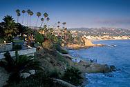 Couple on pathway and Palm Trees and sand beach on the rocky coast at Heisler Park, Laguna Beach, California