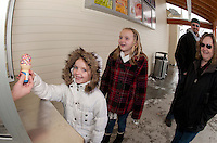 "A cold and wintry day after the storm but Mattison Douville is all smiles as she receives her first ""DQ"" of the season with some extra sprinkles as her sister Alexis waits her turn along with parents Dan and Tammy Friday afternoon.  (Karen Bobotas/for the Laconia Daily Sun)"