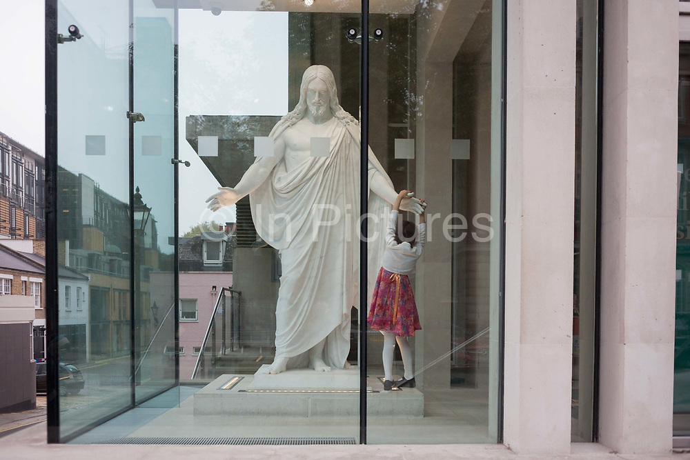A devoted young Christian girl holds the hand of a Jesus statue in the foyer of The Church of Jesus Christ of Latter-day Saints Mormons in central London, England. It is a Sunday morning and members of the Mormon church in Exhibition Road, central London have gathered for their service. The statue of Jesus stands in the corner of the churchs fmodern architecture.