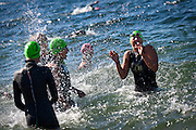 Peyton Bowen, right, of Rathdrum reacts to being splashed by her C.A.S.T. Kroc teammates while warming up for the Steve Omi Memorial Swim at Sanders Beach in Coeur d'Alene on Sunday morning.