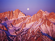 Aerial view of full moon setting between Mount Russell and 14,495 foot Mount Whitney, sunrise over Inyo National Forest with Sequoia National Park beyond, California.