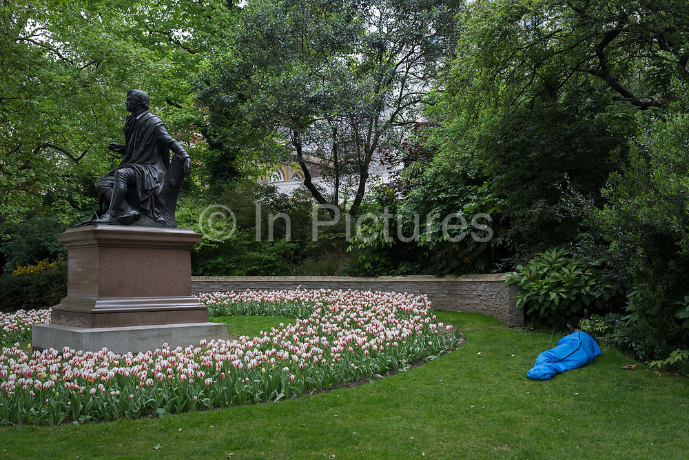 A homeless person in a sleeping bag lies on the grass next to the statue of Scottish poet Robert Burns at the green park space on the Thames Embankment known as Savoy Place, on 4th May 2017, in London, England.