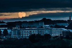 ©Licensed to London News Pictures<br /> Aberystwyth, UK. 20/01/2019. <br /> The first full moon  of 2019 is seen rising over the National Library of Wales in Aberystwyth Wales UK.  The January full moon is sometimes called a 'wolf moon', and is this time also a 'supermoon', being a little closer to the earth and appearing larger and brighter han normal full moons.  In a few hours this moon will be eclipsed by the earth and will appear to glow red in the early morning sky above the UK. Photo credit : Keith Morris / LNP