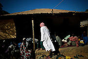 """People gathering around the holy man in Bafata-Oio village, Aladji Fode Mai Toure, expecting his blessing and listening to his advice. Locally known as """"Homem Grande"""", meaning 'great man', serving as a community and local leader. Half of the population are considered to be muslim."""