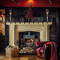 Kirkby Stephen Cumbria. Augill Castle. Interior of lounge with log fire and armchair