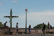A crucified Christ on the cross and local teenagers in Place du Peyrou, Montpellier, south of France.