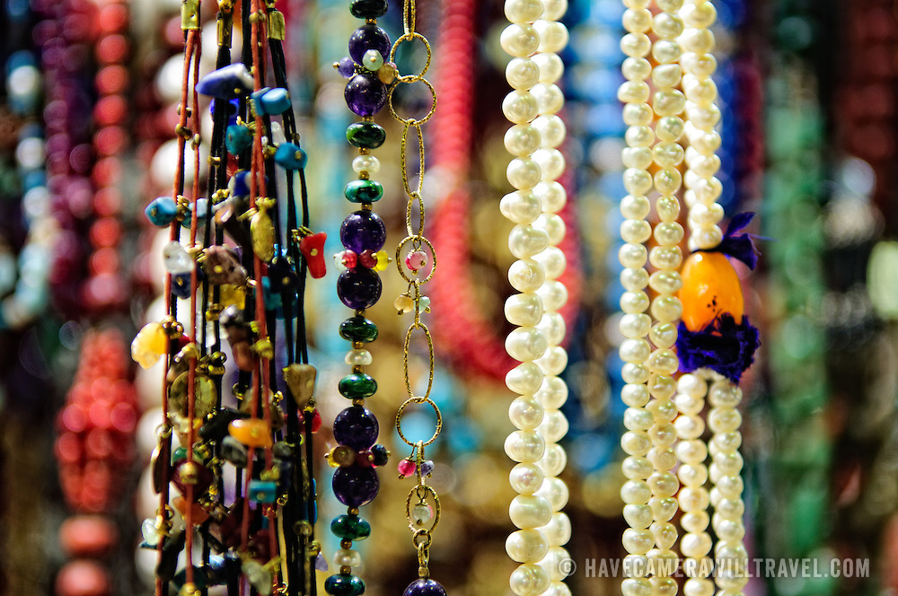 Jewelry and necklaces hang on display for sale in one of the many tiny stores of Istanbul's historic Grand Bazaar, Shallow depth of field.