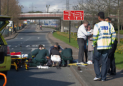 © licensed to London News Pictures. London, UK 11/04/2012. Emergency officers applying heart message to a victim of a traffic accident and trying to comfort his wife on Royal Albert Way in east London. London City Airport announced passengers may experience delays due to this road accident. Photo credit: Tolga Akmen/LNP
