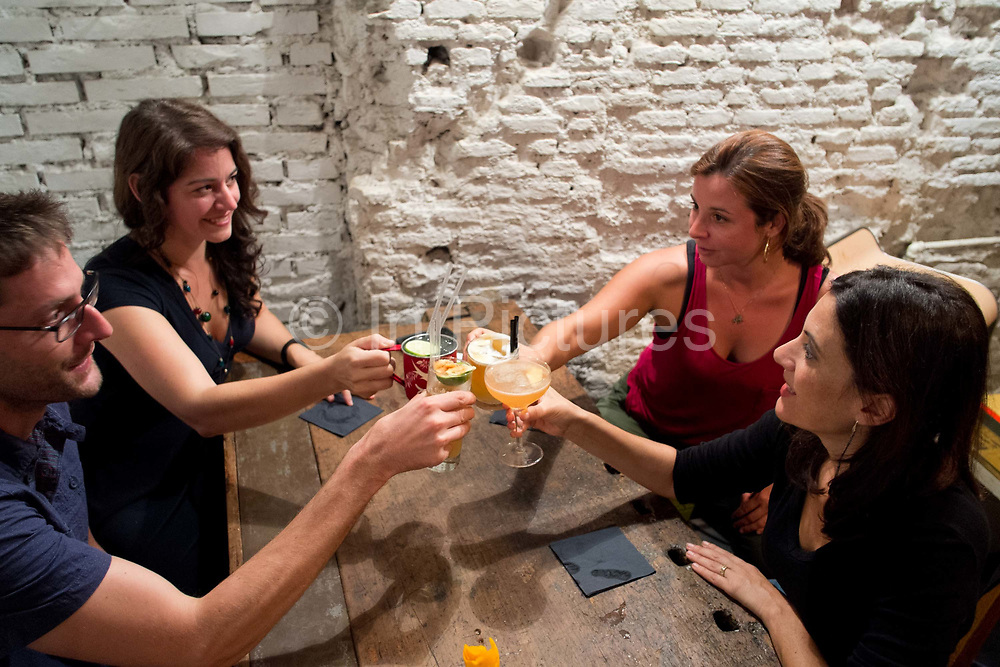 Four friends making a toast and drinking cocktails in a cocktail bar. Barnum / cocktail tours. Rome, Italy.