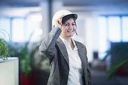 Portrait of a businesswoman smiling in an office and wearing hardhat, Freiburg Im Breisgau, Baden-Württemberg, Germany