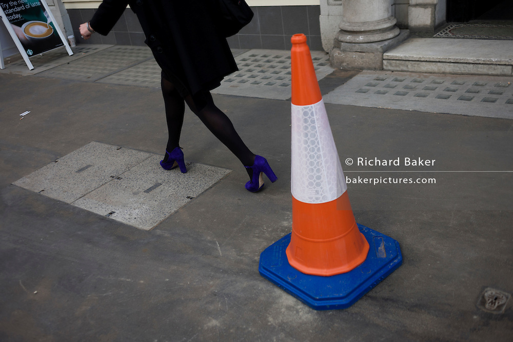 Legs of a woman wearing bright purple shoes walks fast along a London street.
