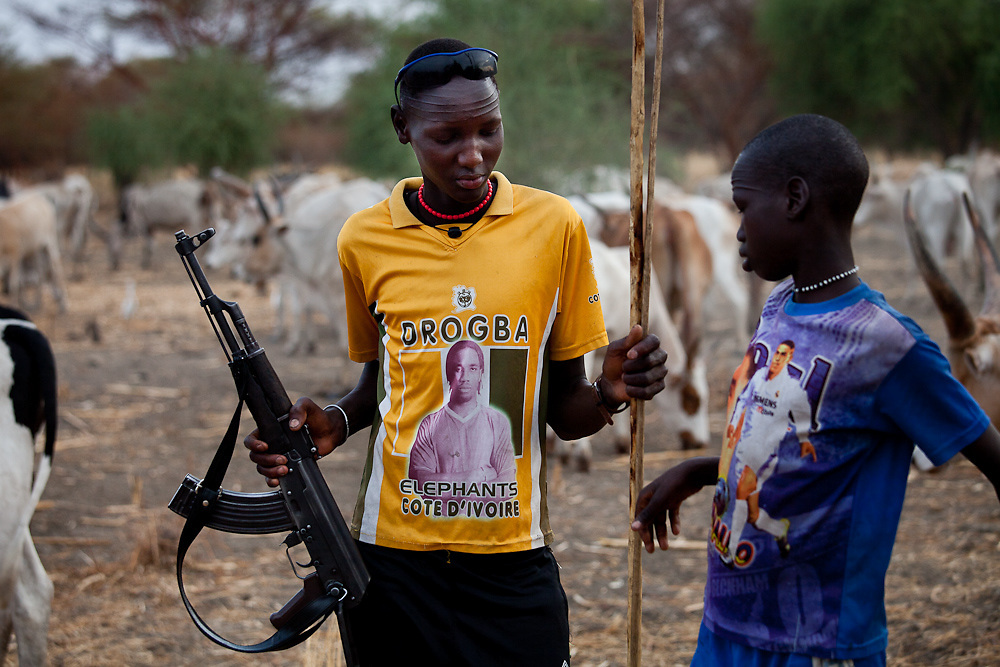 A teenager takes a gun from his younger brother. It is their responsibility to defend the familes' cattle.