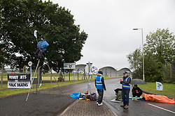 Farnborough, UK. 2nd October, 2021. Extinction Rebellion climate activists are pictured on a steel tripod and locked together using an arm tube in order to block an entrance to Farnborough Airport. Activists blocked three entrances to the private airport to highlight elevated carbon dioxide levels produced by super-rich passengers using private jets and 'greenwashing' by the airport in announcing a switch to sustainable aviation fuel (SAF).