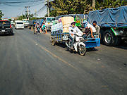 """15 FEBRUARY 2016 - ARANYAPRATHET, SA KAEO, THAILAND:  A motorcycle owner in Aranyaprathet, Thailand, pulls a load of bottled water to the Cambodian side of the border. Thais selling bottled water in the border town of Aranyaprathet, opposite Poipet, Cambodia, have reported a surge in sales recently. Cambodian officials told their Thai counterparts that because of the 2016 drought, which is affecting Thailand and Cambodia, there have been spot shortages of drinking water near the Thai-Cambodian and that """"water shortages in Cambodia had prompted people to hoard drinking water from Thailand.""""    PHOTO BY JACK KURTZ"""