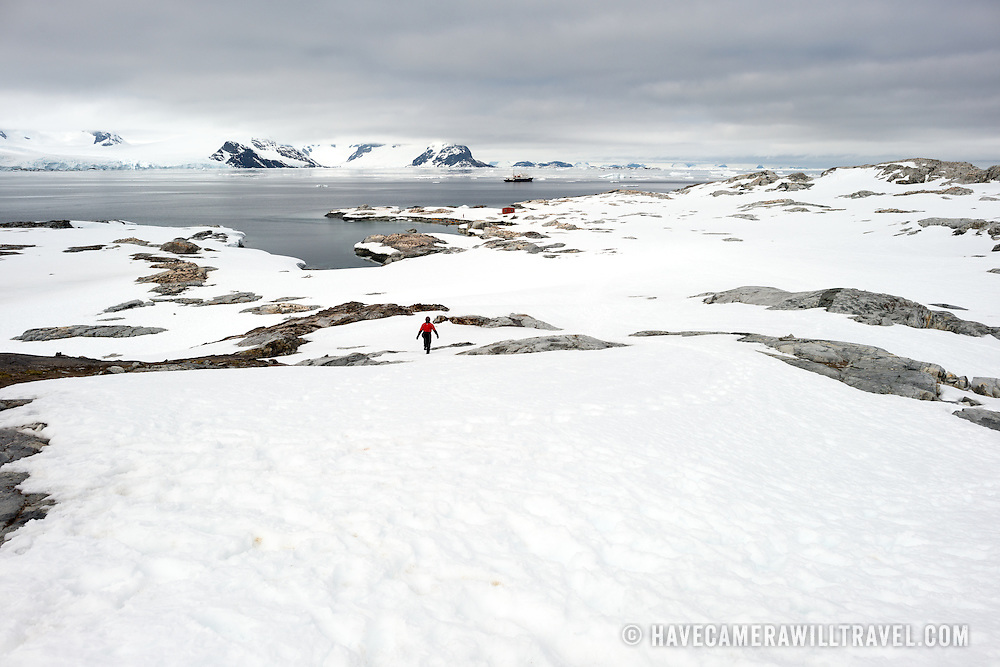 Scenic shot of the snow and rocks of Petermann Island on the Antarctic Peninsula. A cruise ship sits off the shore in the distance.